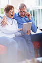 Happy senior couple using digital tablet at home - ZEF001058