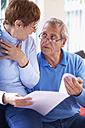 Senior couple reading document at home - ZEF001060