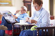 Senior woman knitting with husband in background reading newspaper - ZEF001063
