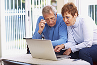 Senior couple using laptop at home - ZEF001072