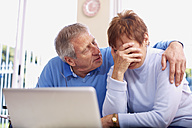 Senior man consoling crying wife at laptop - ZEF001075