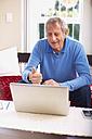 Senior man using laptop at home - ZEF001078