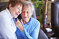 Happy senior couple sharing telephone receiver at home - ZEF001081