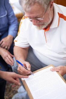Senior man signing document - ZEF001087