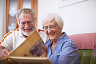 Senior couple at home looking at photo album - ZEF001090