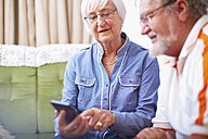 Senior couple with smart phone at home - ZEF001095