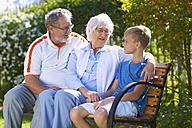 Grandparents and grandson sitting on park bench - ZEF001113
