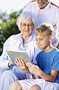 Grandson and grandparents using digital tablet - ZEF001116