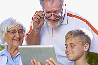Grandson and grandparents using digital tablet - ZEF001118