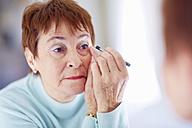 Senior woman applying make-up - ZEF001164