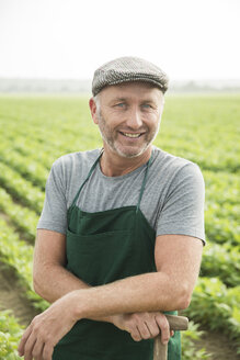 Portrait of smiling farmer standing in front of a field - UUF002026