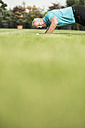 Golf player kneeling on turf looking at golf ball - UUF002039