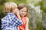 Boy whispering into girl's ear - WESTF020100