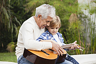 Grandfather and grandson with guitar outdoors - WESTF020103