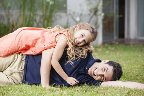 Playful father and daughter lying in grass - WESTF020114