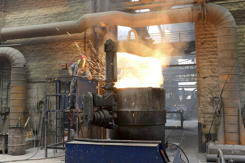 Worker checking temperature of material in a foundry - SCH000434
