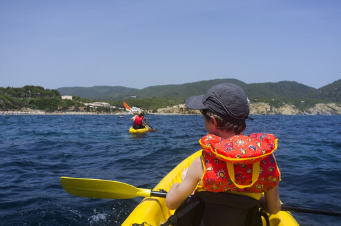 Spain, Balearic Islands, Ibiza, Es Figueral, young boy sitting in a kayak - TKF000409