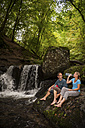 Germany, Rhineland-Palatinate, Moselsteig, Ehrbachklamm, couple resting at waterfall - PAF001003