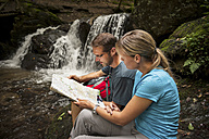 Germany, Rhineland-Palatinate, Moselsteig, Ehrbachklamm, couple reading map at waterfall - PAF000998