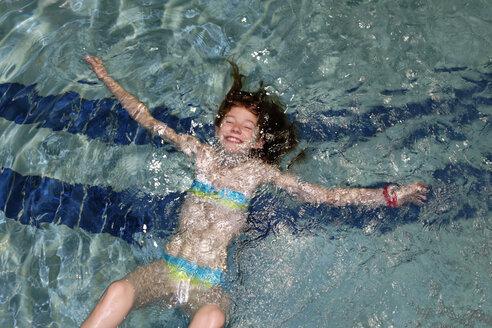 Smiling girl swimming backstroke in a pool - LBF000967