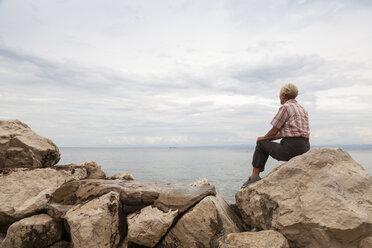 Slovenia, Piran, woman sitting on rocks at waterside looking at horizon - WIF001112