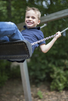Portrait of smiling boy sitting on a swing - SHKF000001