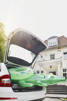 Germany, Hesse, Frankfurt, Swim toys packed in car in front of villa - RORF000040
