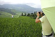 China, Guangxi, mother taking picture of daughter in rice field - DSG000193