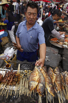 China, Erhai lake, Little Putuo island, man selling grilled fish - DSG000221