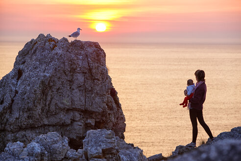 France, Brittany, Pointe de Pen-Hir, Woman with child watching sunset - DSG000870