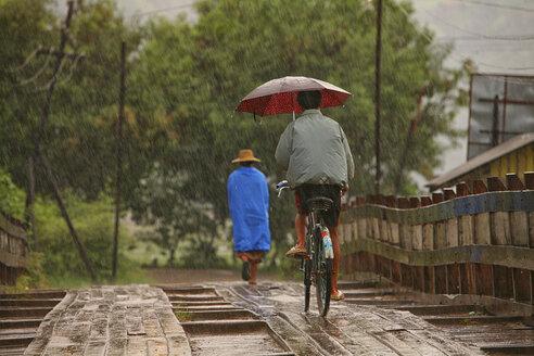 Myanmar, people on footbridge in monsoon rainfall - DSG000350