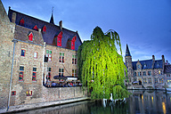 Belgium, Bruges, People sitting at canal at blue hour - DSGF000564