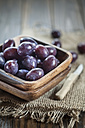 Wooden bowl of figs and a kitchen knife on jute - SBDF001305