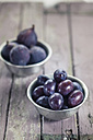 Two metal bowls of figs and plums on wood - SBDF001308