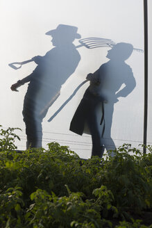 Silhouette of man and woman holding rake and fork - ZEF001203