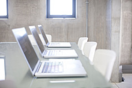 Row of three laptops on a table in an office - ZEF001216