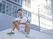 Smiling jogger with earphones sitting on stairs - MAD000069