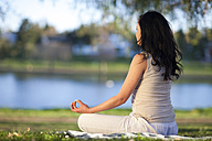 Young woman doing yoga exercise in a park - ZEF001224