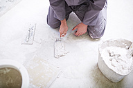 Construction worker with tiling trowel - ZEF001823