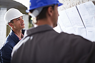 Construction workers discussing building plans - ZEF001831