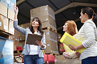 Woman with clipboard in warehouse talking to women - ZEF001434