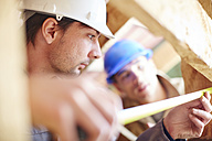 Construction workers measuring roof beams - ZEF001847