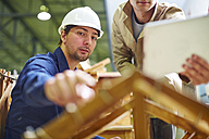 Construction worker and foreman discussing roof beams - ZEF001849