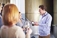 Man presenting bottle of wine on shop floor - ZEF001460