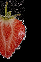 Sliced strawberry with air bubbles in front of black background, close-up - MJOF000820