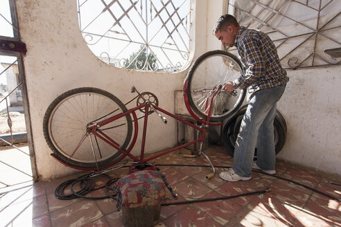 Cuba, Matanzas, Jaguey Grande, young man working at bicycle repair shop - NN000071