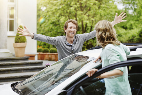 Happy man with outstretched arms looking at woman at car - RORF000115