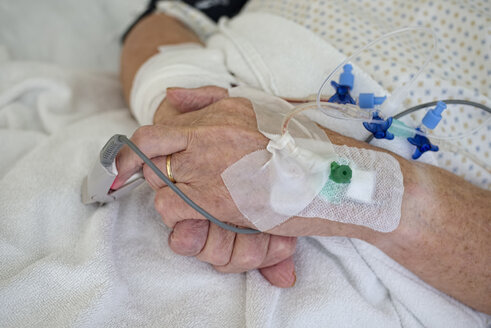 Hands of senior man with cannulae and band-aid being in intensive care - LAF001088