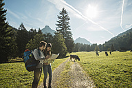 Austria, Tyrol, Tannheimer Tal, two young  hikers with hiking map - UUF002110