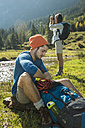 Austria, Tyrol, Tannheimer Tal, two young  hikers relaxing - UUF002121